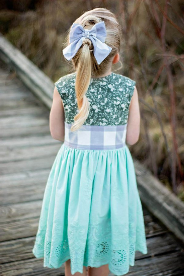 Opal vintage girls dress, green patterned top, big blue gingham waistband and matching bow, tea length blue skirt with lace hem.