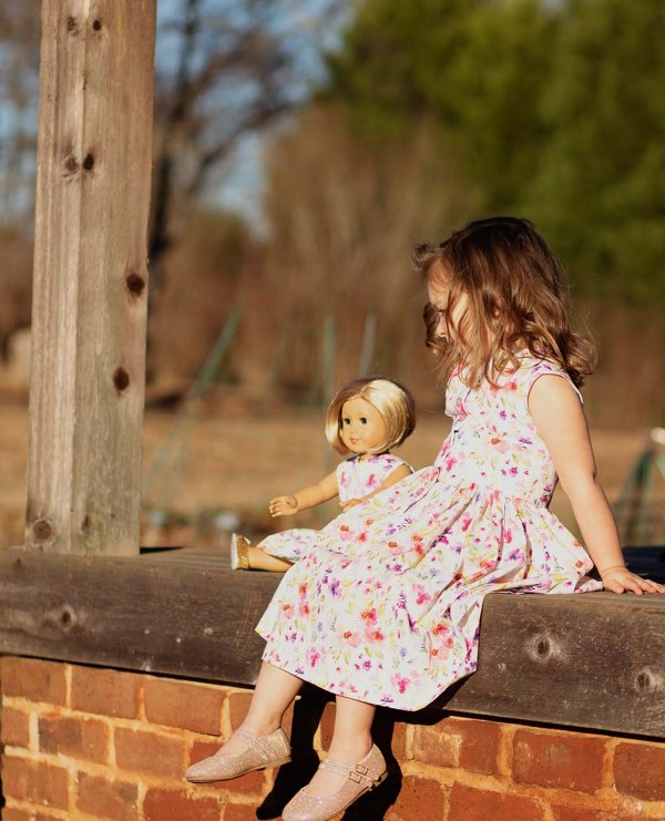little girl and doll enjoying sunshine in their matching Opal dresses